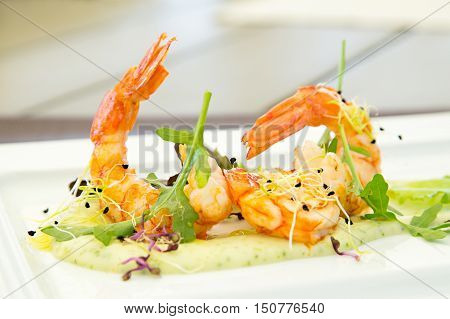 Gourmet appetizer with shrimp, sauce and arugula