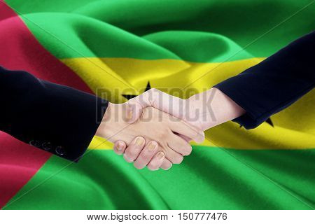 Picture of business handshake with two worker hands shaking hands in front of a national flag of Sao Tome and Principe