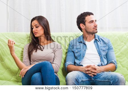 Young couple is sitting on sofa at home and they are getting bored.