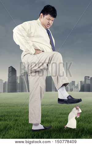 Overweight businessman trampling down his rival on the meadow shot outdoors