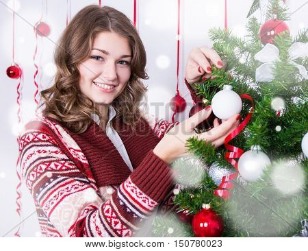 Portrait Of Happy Young Woman Decorating Christmas Tree