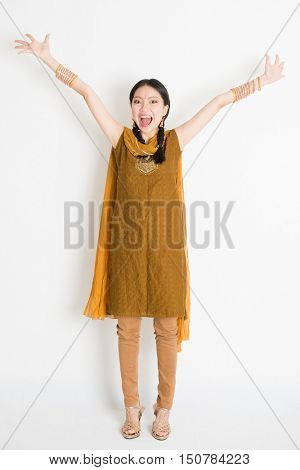 Portrait of excited mixed race Indian Chinese woman in traditional punjabi dress arms outstretched, full length standing on plain white background.