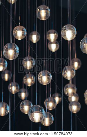 lighting balls on the chandelier in the lamplight light bulbs hanging from the ceiling lamps on the dark background selective focus vertical