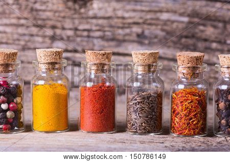 Indian pices in bottles on wooden background