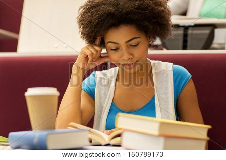 education, high school, university, learning and people concept - bored african student girl with books and coffee on lecture