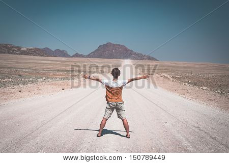 Woman With Outstretched Arms Standing On Gravel Road Crossing The Namib Desert, In The Namib Naukluf