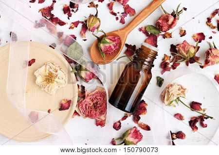 Essential rose oil, dried rose petals, aroma dropper bottle, wooden preparation utensils. Natural beauty care.