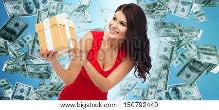people, holidays, birthday and finances concept - beautiful sexy woman in red dress with gift box over dollar money rain on blue background