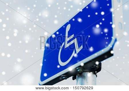 winter, traffic laws and highway code concept - close up of road sign for disabled outdoors over snow