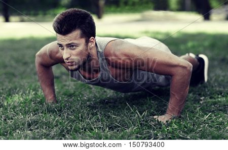 fitness, sport, exercising, training and lifestyle concept - young man doing push ups on grass in summer park