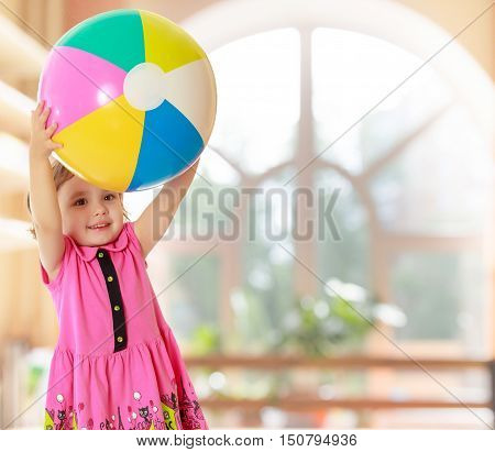 Caucasian little girl in a short pink dress , holding up a big ball.On the background of the great hall of the kindergarten with a semicircular window.