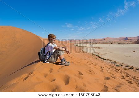 Relaxed Tourist Sitting On Sand Dunes And Looking At The Stunning View In Sossusvlei, Namib Desert,