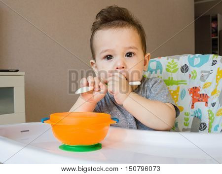 Baby Eating Food With A Spoon, Toddler Eating Messy And Getting Dirty, Infant Having Oatmeal As Brea
