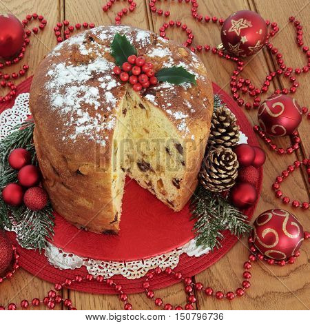 Panettone christmas cake, holly, red bauble decorations with bead strands over oak table background.