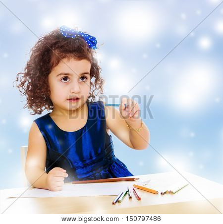 Pensive little girl in a blue dress, holding a pencil . She paints at a table in a Montessori kindergarten.Blue winter background with white snowflakes.