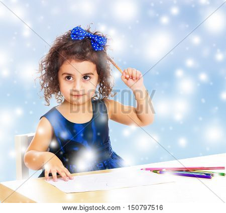 Beautiful little curly girl in blue dress draws the table in a Montessori kindergarten. The girl thoughtfully looks up.Blue winter background with white snowflakes.