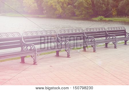 Autumn romantic bench. Cast iron benches with wooden flooring on the background of city Park with lake. Early morning fog. Sad time of year. Waiting past.