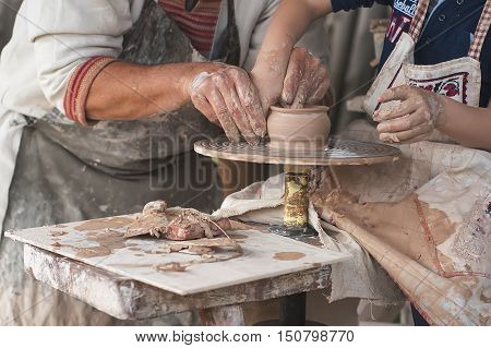 Hands of two people create pot on potter's wheel. Teaching ukrainian traditional crafts. Focus on the hands