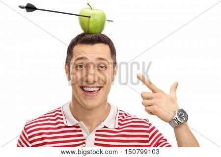 Delighted man pointing at an apple pierced by an arrow on his head isolated on white background