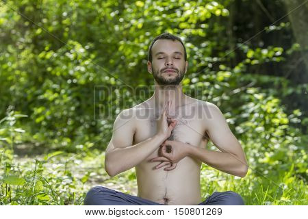 Young Man Meditating Surrounded By Tropical Trees And Bushes