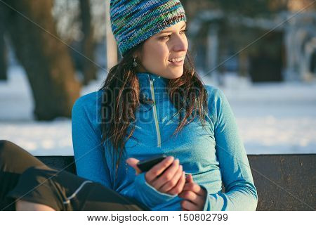 Serene lady texting on a smartphone after a winter workout