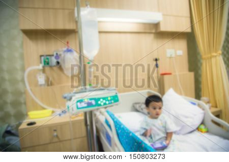 Blur Illness asian boy sitting on sickbed in hospital with infusion pump intravenous IV drip.