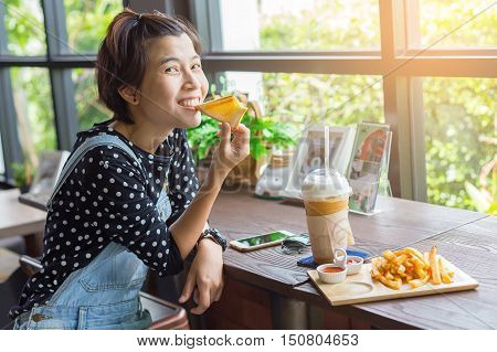 Beautiful Asian woman happy While eating, coffee, Snacks in Coffee shop