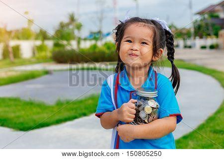 portrait of happy young little girl hugs coins glass bottle ,saving money concept ,Education, school concept. Junior Savings Account concept