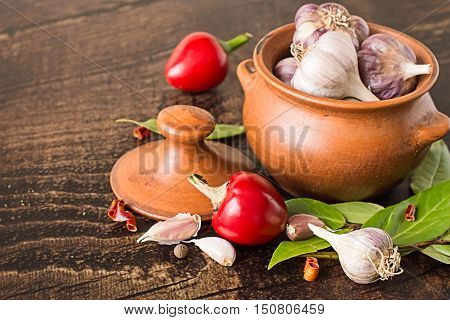 Clay pot with heads of garlic, pods of red bitter pepper and fresh bay leaves on a brown wooden table.