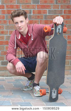 Portrait of a cool young teenage boy outdoors with skateboard