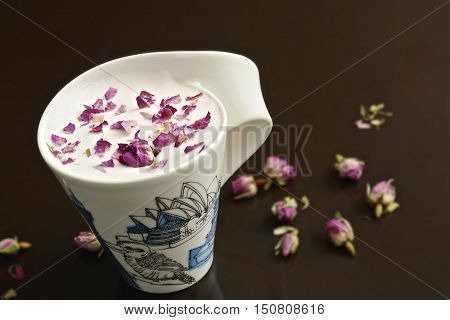 Cup of rose tea with rose bud on black background