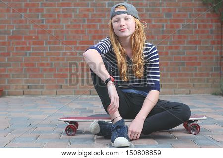Portrait of a cool young teenage girl outdoors with skateboard
