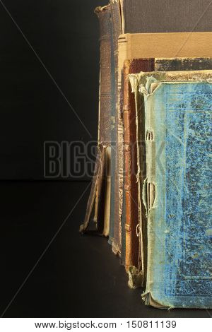 Stack of old books, copyspace for your text. Antique books on old wooden shelf.