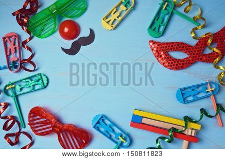 Jewish holiday purim background with carnival mask party costume and noisemaker. View from above