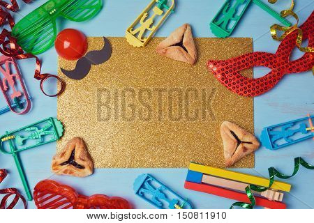 Purim golden glitter background with carnival mask party costume and hamantaschen cookies. View from above