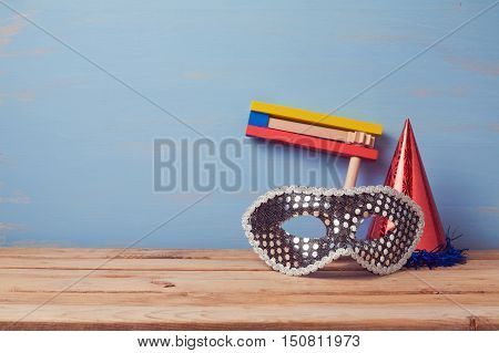 Jewish holiday purim background with carnival mask hat and noisemaker gragger on wooden table