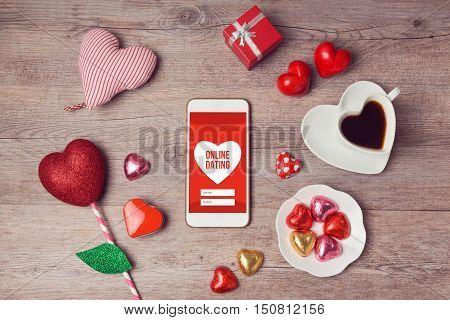 Online dating cocept with smartphone mock up and heart chocolates. Valentine's day romantic celebration. View from above