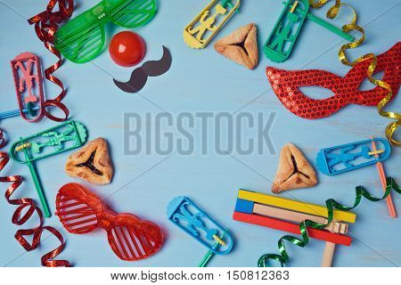 Purim background with carnival mask party costume and hamantaschen cookies. View from above