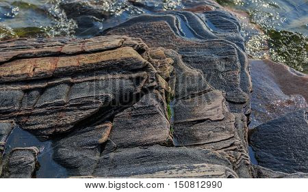 fragment of amazing splendid gorgeous closeup view of natural stone rock surface, looks like art in lake water