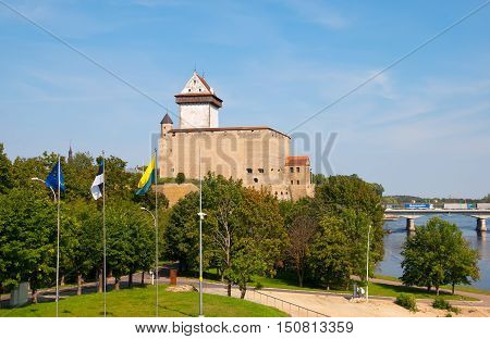 NARVA, ESTONIA - AUGUST 21, 2016: Hermann Castle (Hermannsfeste) on the bank of The Narva (Narova) River. On the right side is The Bridge of Friendship between Estonia and Russian Federation