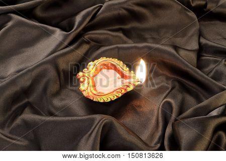 Handmade Diwali Clay Lamp on Black Satin Background