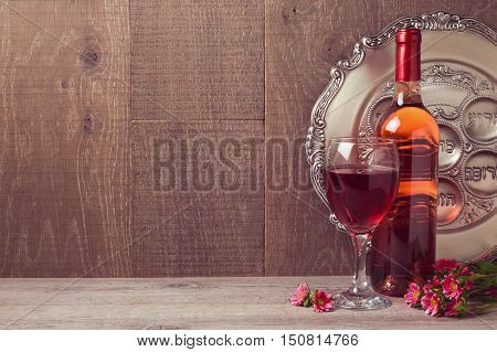 Passover celebration with wine and seder plate over wooden background