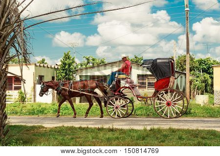 Cayo Coco island village, Cuba, July 23, 2013, Local Cuban village man making his living by providing a transportation as a taxi , using his horse-drawn carriage daily