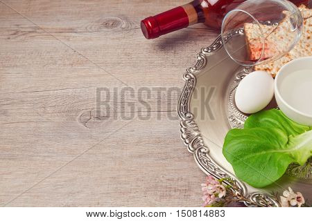 Passover (pesah) background with seder plate matzoh and wine over wooden background