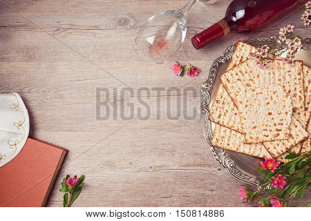 Jewish holiday Passover background with matzah seder plate and wine. View from above