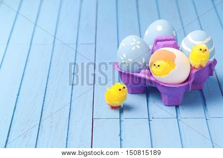 Easter holiday creative background with painted eggs and easter cute chicks