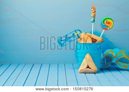 Purim traditional gifts with hamantaschen cookies noisemaker and carnival mask on blue background
