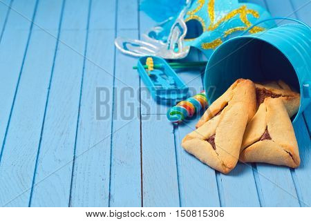 Hamantaschen cookies in bucket for Purim holiday on blue wooden background