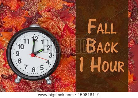 Daylight Savings Time message Some glittery fall leaves and retro alarm clock with text Fall Back 1 Hour 1 Hour 3D Illustration