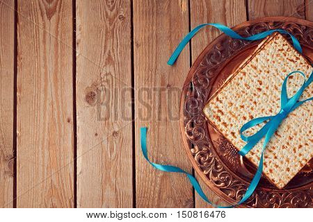 Jewish holiday Passover background with matzo and vintage seder plate. View from above